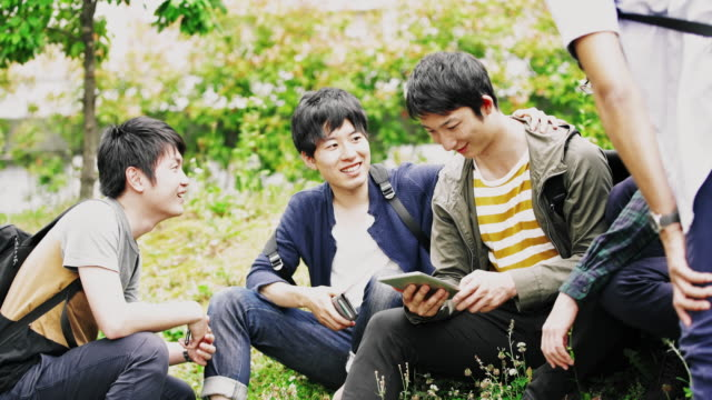 ws japanese students using digital tablet in the park - studente universitario video stock e b–roll