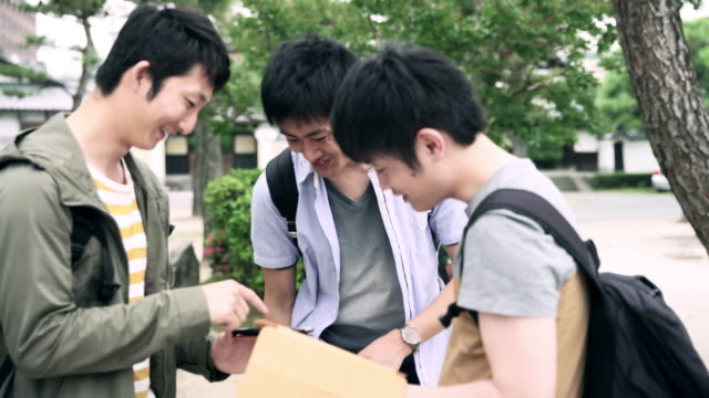 ms japanese students using smartphone and digital tablet - three people stock videos & royalty-free footage