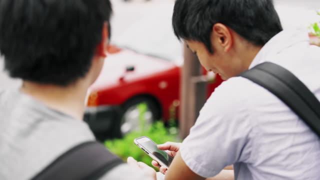 CU の日本人学生がバスを待っている間にスマート フォンを使用して