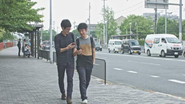 自分の携帯電話をチェック通りを歩いて日本の学生