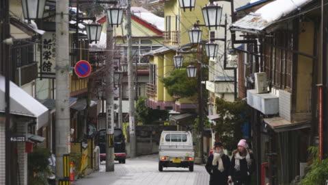 japanese style houses and ryokan (traditionaljapaneseinn) stand along the both side of the street at shibu onsen (shibu hot spring) yamanouchi-machi, nagano japan on feb. 21 2019. - 路地点の映像素材/bロール