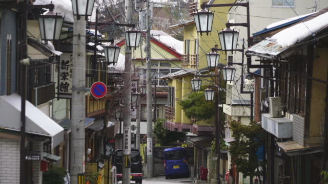 japanese style houses and ryokan (traditional japanese inn) stand along the both side of the street at shibu onsen (shibu hot spring) yamanouchi-machi, nagano japan on feb. 21 2019. - jigokudani monkey park stock videos & royalty-free footage