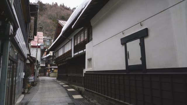 vídeos de stock e filmes b-roll de japanese style houses and ryokan (traditional japanese inn) stand along the both side of the stone pavement alley at shibu onsen (shibu hot spring) yamanouchi-machi, nagano japan on feb. 18 2019. - fonte termal
