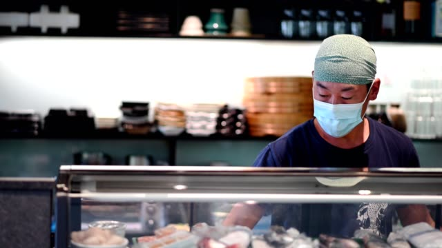 japanese sushi chef wearing a mask for covid-19 - food and drink establishment stock videos & royalty-free footage