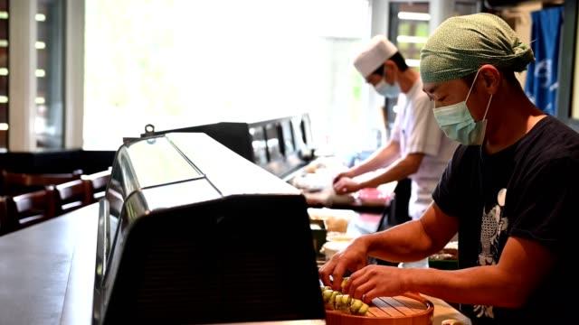 stockvideo's en b-roll-footage met japanse sushikoks die een maskers voor covid-19 dragen - heropening