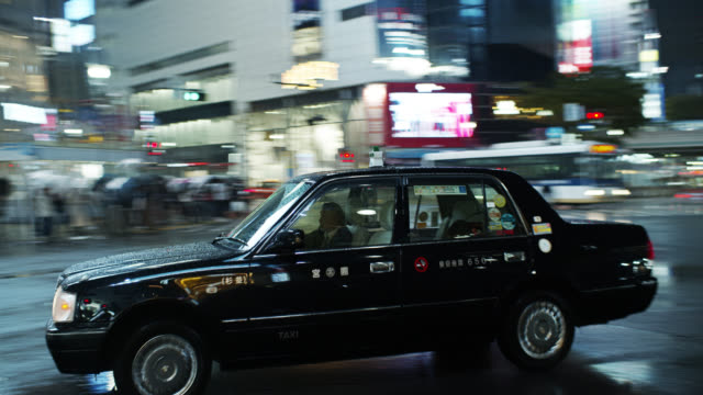 japanese taxi in shibuya crossing on rainy night - 移動中点の映像素材/bロール