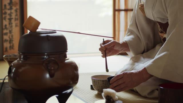 vídeos de stock, filmes e b-roll de anfitrião japonês da cerimónia do chá que mede para fora o pó - washitsu