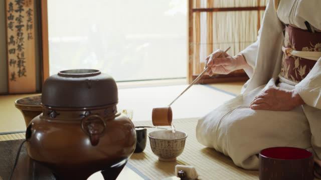 vídeos y material grabado en eventos de stock de ceremonia del té japonesa anfitrión verter agua en el tazón - sado