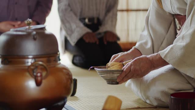 vídeos y material grabado en eventos de stock de anfitrión de la ceremonia del té japonesa con invitados en background - sado