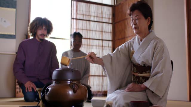 日本茶マスターは2人の観光客のためにお茶を作る - tourist点の映像素材/bロール