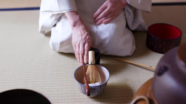 vídeos y material grabado en eventos de stock de maestro de té japonés preparándose para hacer una taza de té matcha tradicional - sado