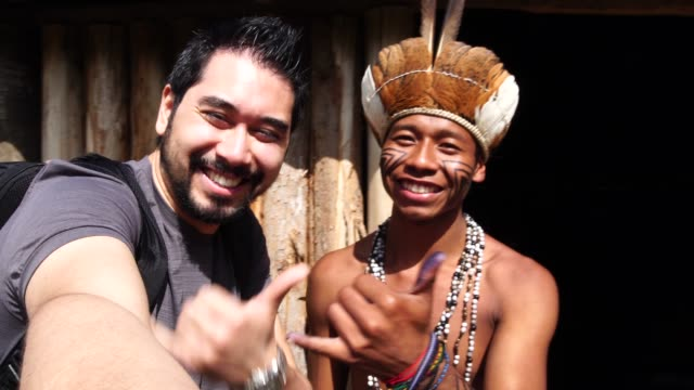 vídeos de stock e filmes b-roll de japanese tourist taking a selfie with indigenous brazilian man, from guarani ethnicity - estrada da vida