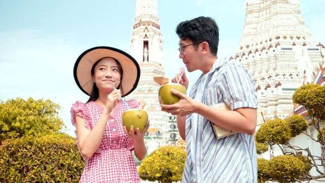 日本の touristor はタイ寺院 (ワット・アルーン) を訪問し、ココナッツウォーターを飲みます. - 里山点の映像素材/bロール