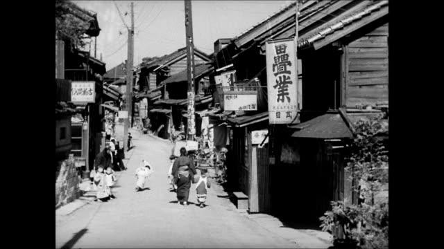 japanese town woman walking w/ child children playing on street. int man painting turning pottery. boy churning paint in bowl. man painting working... - village stock videos & royalty-free footage