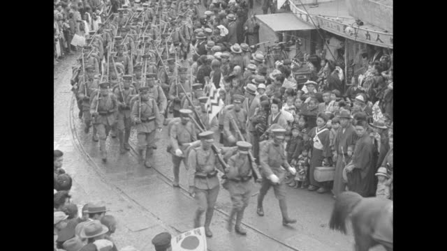 japanese troops lined up in square in nagoya, crowd with umbrellas watching, as they prepare to depart for the tsinan front in china, possibly... - 日本の軍事力点の映像素材/bロール