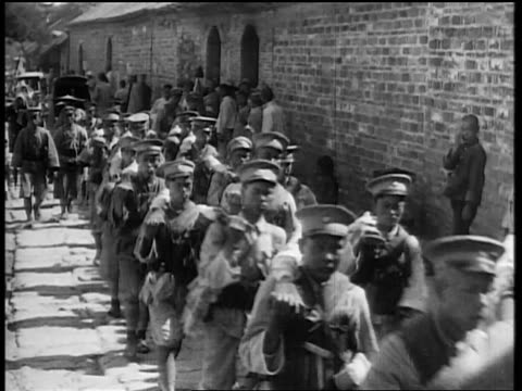 Japanese troops marching alongside wall / Japan invading Manchuria