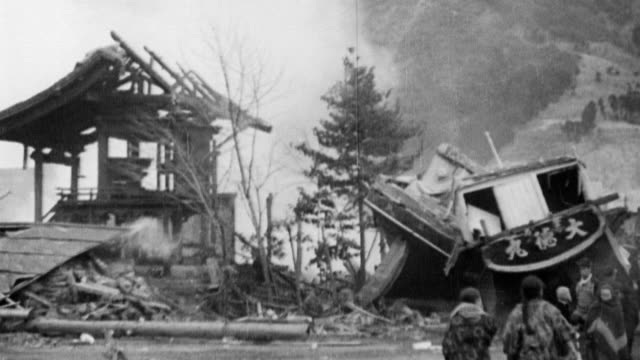 vidéos et rushes de japanese villagers walking around searching through smoldering debris after earthquake tidal wave and fire destroys hundreds of towns / people... - 1933