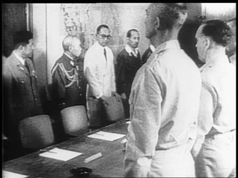 Japanese weapons lay on a desk outside the conference pistols and swords / the Americans enter the conference room stand behind chairs / Lieutenant...