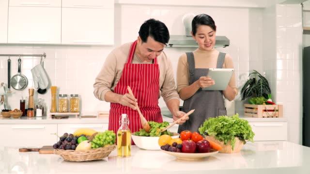 日本人の奥さんと夫デジタル タブレットから助言を得ることによって一緒に料理しよう - preparing food点の映像素材/bロール