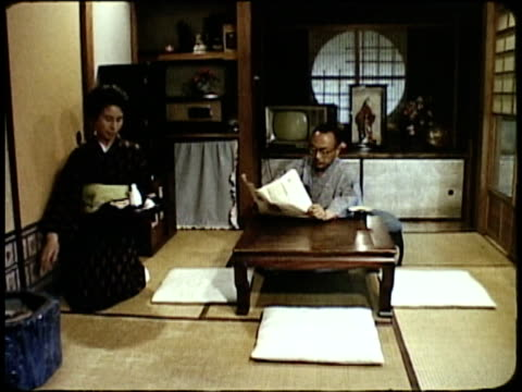 1963 montage japanese wife serving her husband saki / japan  - tatami mat stock videos and b-roll footage