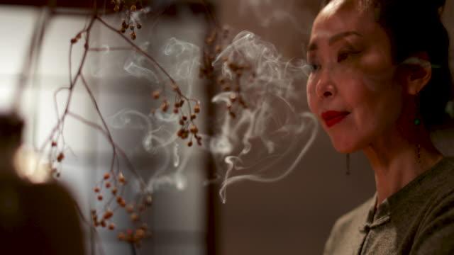 japanese woman at home contemplating and smelling incense, kyoto japan - アロマ点の映像素材/bロール