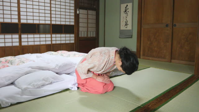 Japanese Woman Bowing in a Ryokan