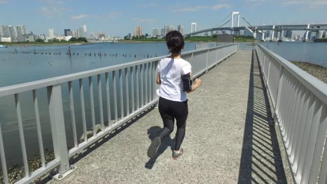 japanische frau rundet ihren lauf im park - off track laufen stock-videos und b-roll-filmmaterial