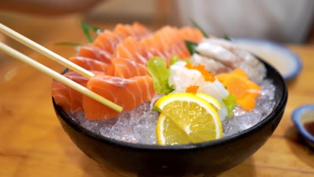 日本の女性がサーモン刺身の生を醤油に浸す - 居酒屋点の映像素材/bロール