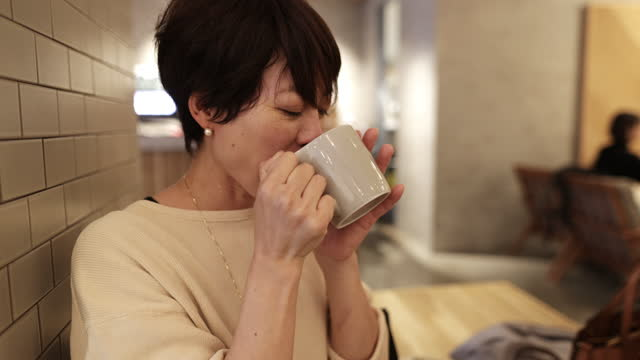 vídeos y material grabado en eventos de stock de mujer japonesa bebiendo una taza de café en café - pausa del café