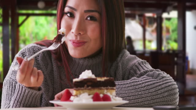 Japanese woman eating cake at a restaurant