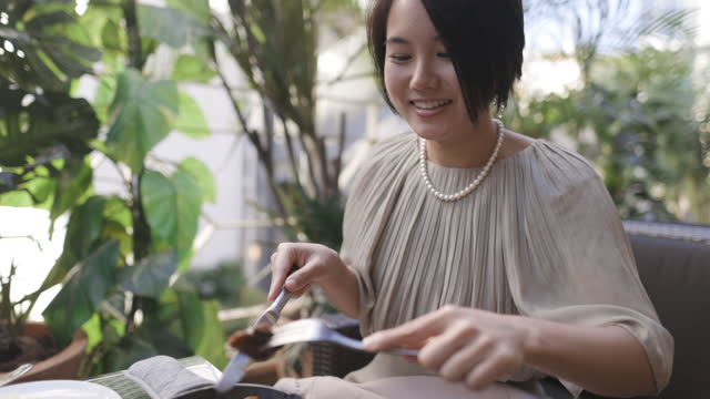 japanese woman eating hamburger steak for lunch at outdoor cafe - straight hair stock videos & royalty-free footage