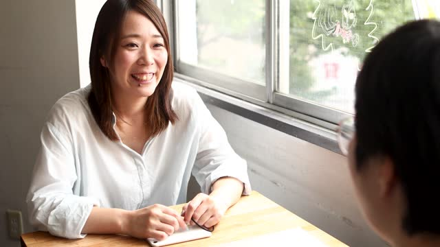 a japanese woman enjoys chatting with a friend at a cafe - 35 39 years stock videos & royalty-free footage