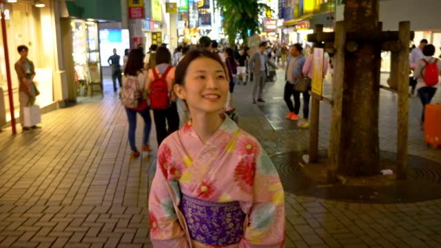 Japanische Frau im Kimono zu Fuß an einer verkehrsreichen Strasse
