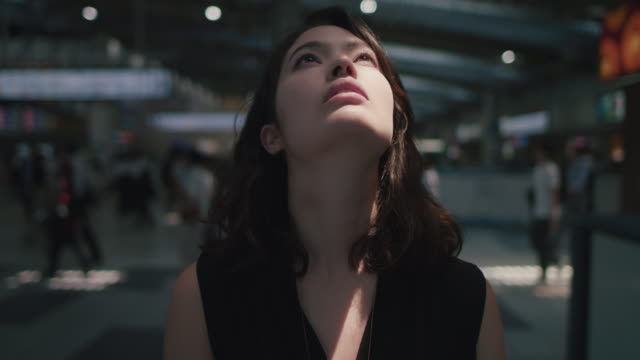 japanese woman in in train station in tokyo, japan with closed eyes - eyes closed stock videos & royalty-free footage