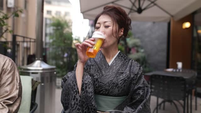 アウトドアカフェでビールを飲む着物を着る日本人女性 - のみ点の映像素材/bロール