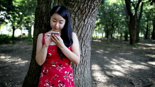 赤いドレスの日本女性がスマート フォンを使用してください。 - 赤のドレス点の映像素材/bロール
