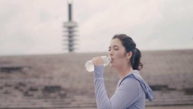 japanese woman in sports bra and hooded shirt drinking water in tokyo, japan. - 飲む点の映像素材/bロール