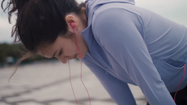 vidéos et rushes de japanese woman in sports clothing bending over breathing in tokyo, japan. - inhaler