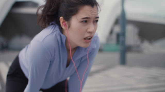 japanese woman in sports clothing catching breath after run in tokyo, japan. - inhaling stock videos & royalty-free footage