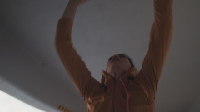 vídeos de stock, filmes e b-roll de japanese woman in sports clothing jumping to reach ceiling in tokyo, japan. - esforço