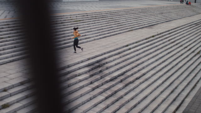 japanese woman in sports clothing running up steps in tokyo, japan. - rennen körperliche aktivität stock-videos und b-roll-filmmaterial