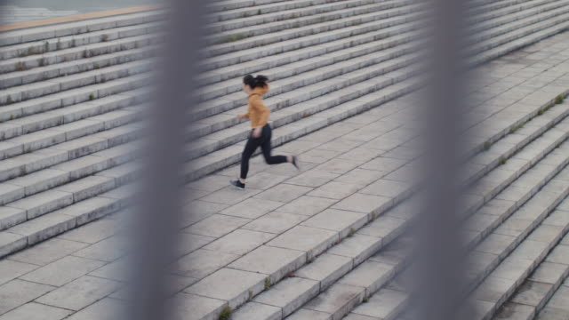 japanese woman in sports clothing running up steps in tokyo, japan. - potere femminile video stock e b–roll