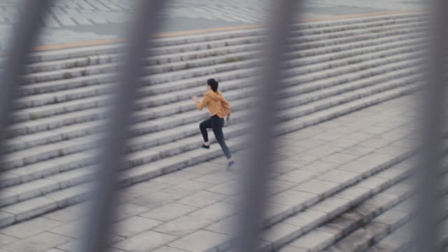Japanese woman in sports clothing running up steps in Tokyo, Japan.