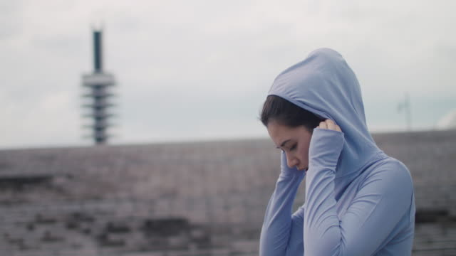 vidéos et rushes de japanese woman in sports clothing with hood and headphones taking off for runin tokyo, japan. - décision
