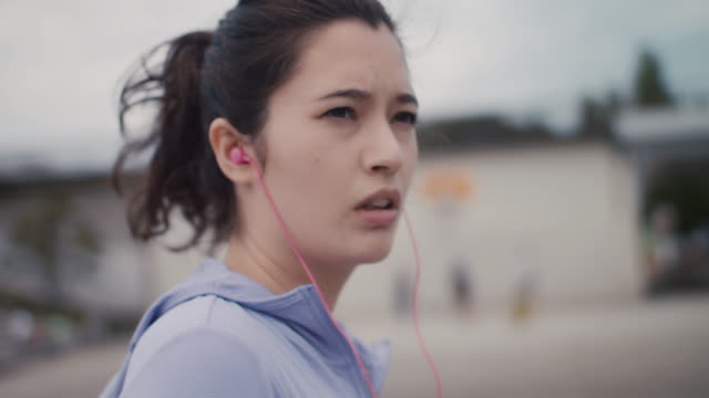 Japanese woman in sports clothing with pink headphones walking in Tokyo, Japan.