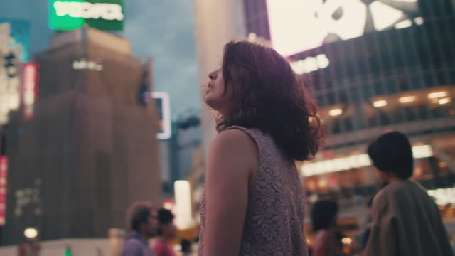 Japanese woman in the middle of busy intersection looking up / Tokyo, Japan