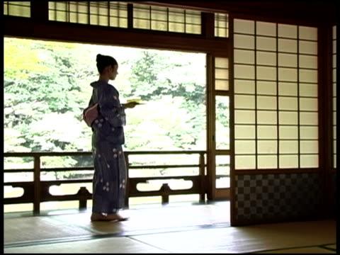 Japanese Woman In Yukata Carrying Tea In a Traditional House,Fukuoka, JapanJapanese woman in kimono