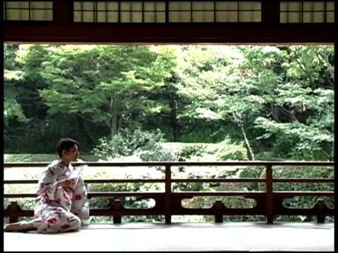 Japanese Woman In Yukata Faning Herself On Terrace By Forest, Fukuoka, JapanJapanese woman in kimono