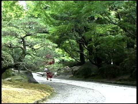 Japanese Woman in Yukata Walking Down Stone Path In Forest,Fukuoka, JapanJapanese woman in kimono
