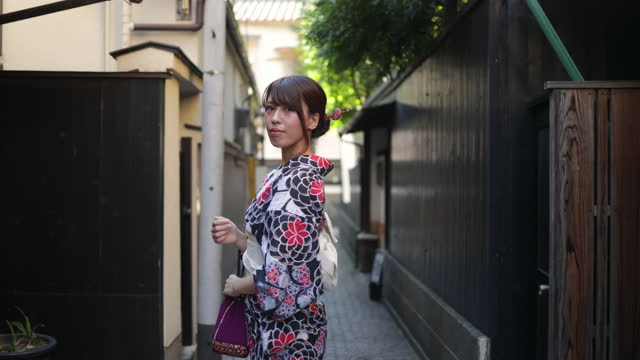 japanese woman in yukata walking on narrow path - rear view and looking over shoulder - three quarter length stock videos & royalty-free footage